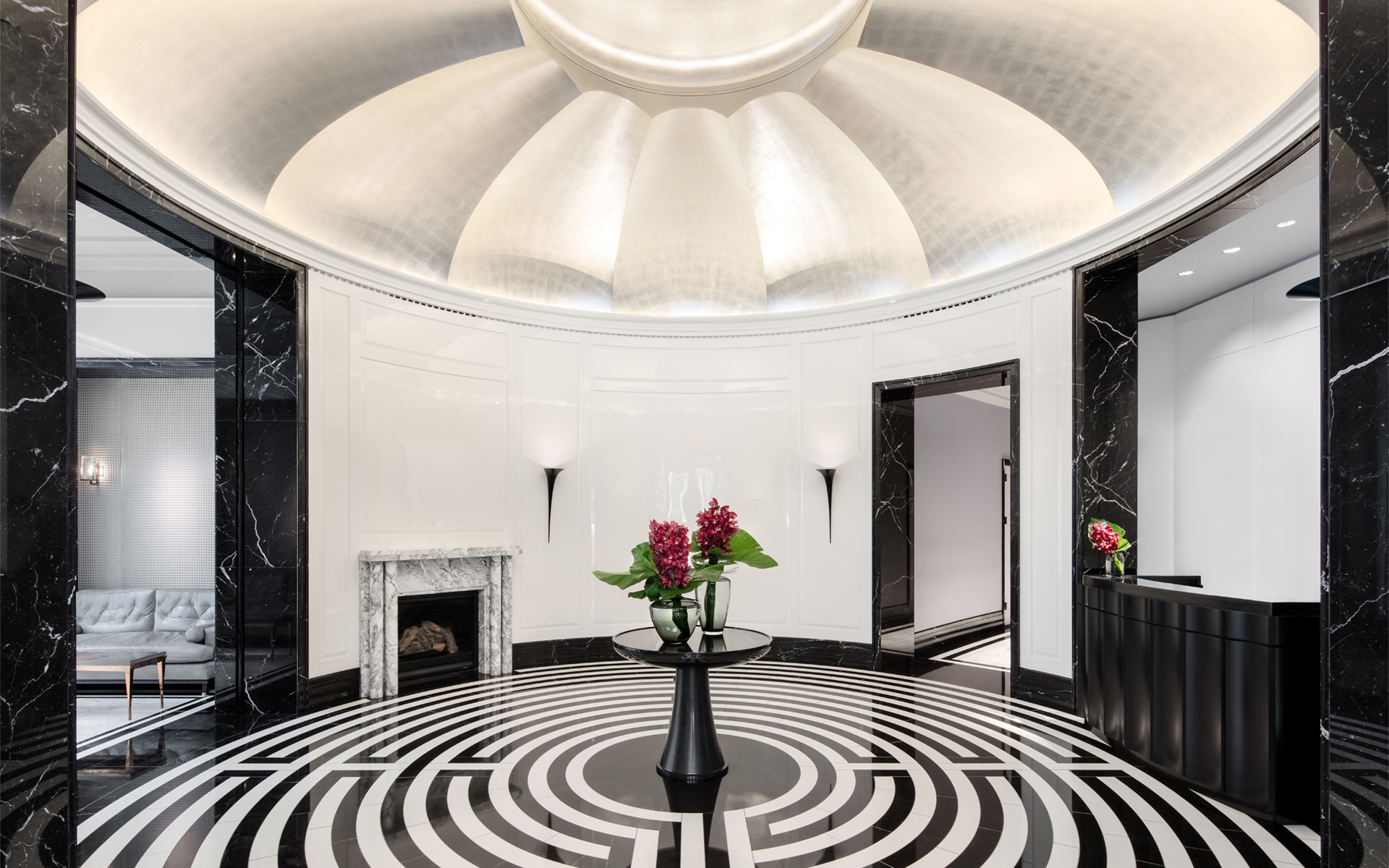 Private residential lobby with labyrinth-patterned stone floor, white lacquer walls, silver leaf rotunda ceiling, and fireplace.