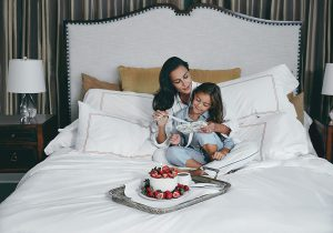 Mother and daughter enjoying breakfast in bed